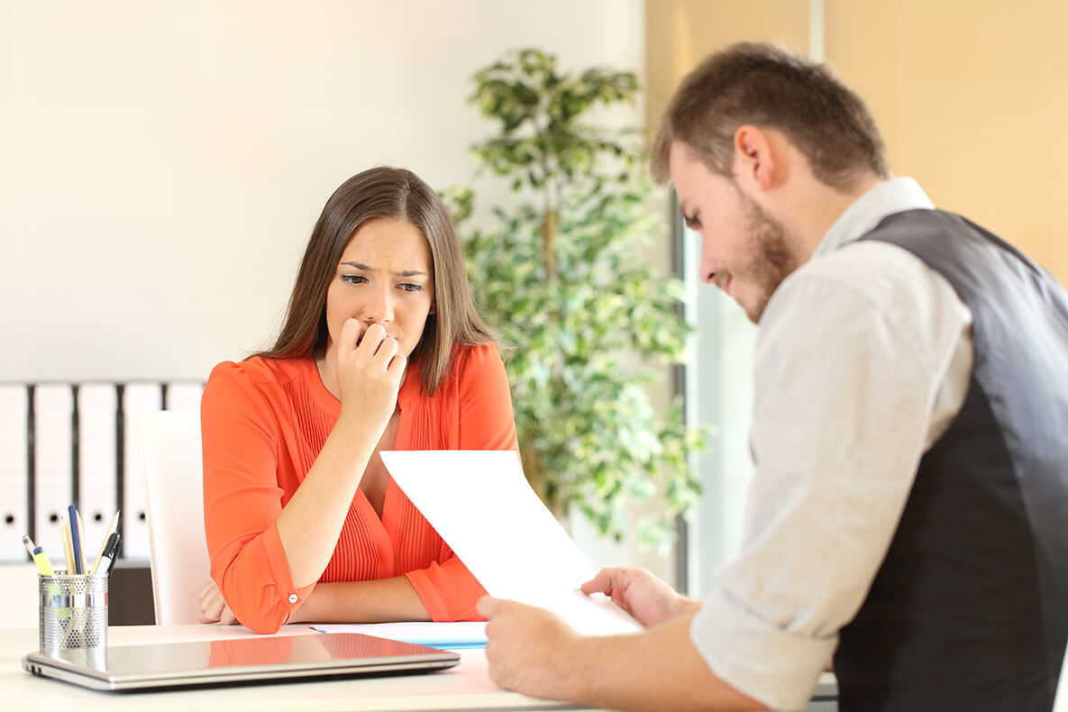 Nervous woman looking at manager reading her resume during a job interview at office