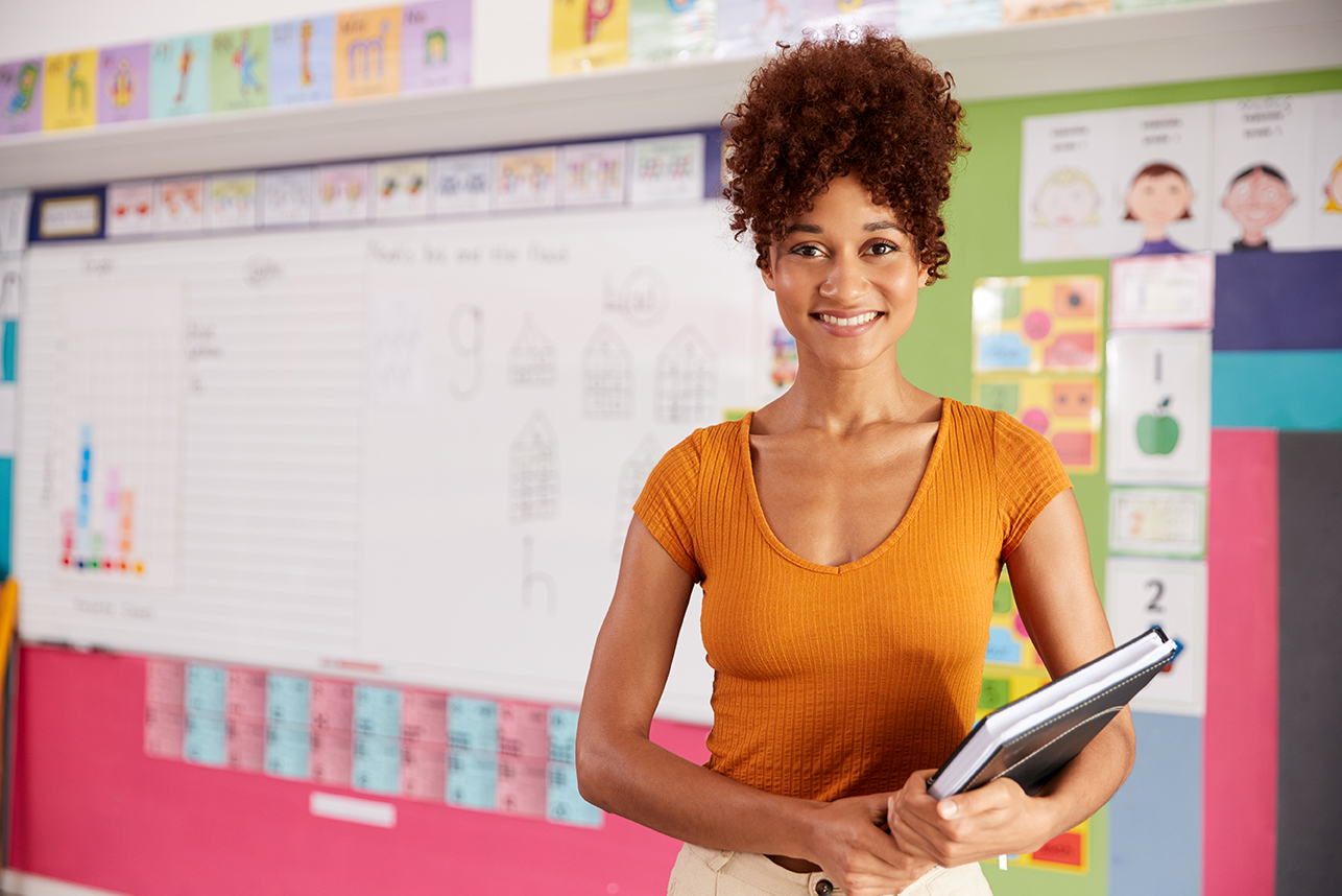 Portrait Of Female Elementary School Teacher Standing In Classroom